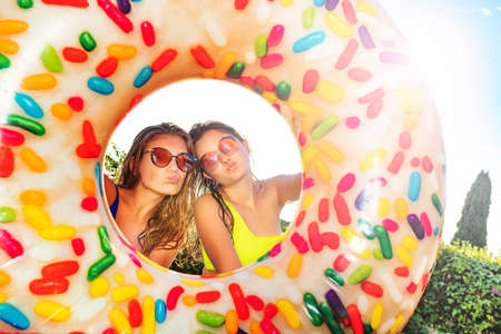 Two teen girls with kiss funny expression look from inflatable doughnut wearing sunglasses standing in the garden over sky Reklamní fotografie