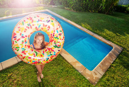 Happy smiling teen girl stand with inflatable buoy doughnut on the border of swimming pool view from above