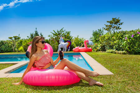 Beautiful girl with soda in hand and sun glasses lay on the pink flamingo near swimming pool in the garden