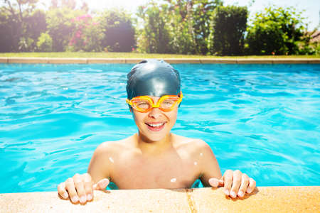 Cute little boy in swimming cap and googles lay on the border of outdoor pool look at camera smiling Reklamní fotografie