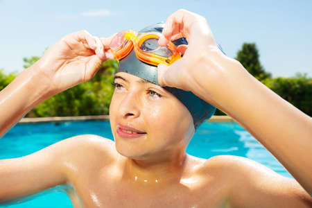 Close-up portrait of a little boy in swimming cap hold googles with hands on the border of outdoor pool look at camera smiling Reklamní fotografie