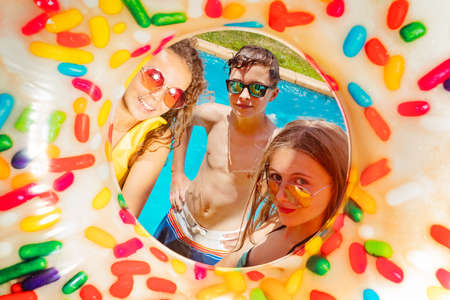 Three young kids inside the inflatable buoy smile wearing near swimming pool in sunglasses with nice smiles