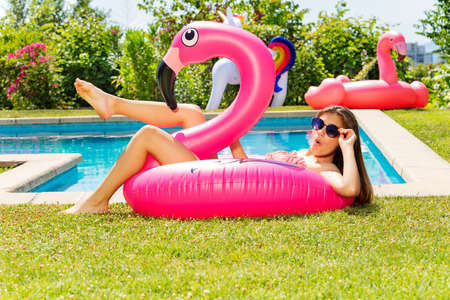 Surprised happy relaxed girl lay on the pink flamingo inflatable toy buoy near swimming pool Reklamní fotografie