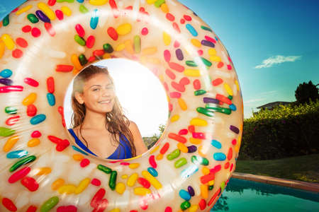 Happy beautiful smiling girl portrait in inflatable buoy doughnut near swimming pool Reklamní fotografie