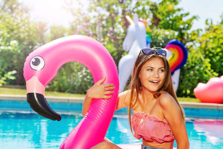 Happy smiling girl portrait with pink flamingo inflatable toy buoy near swimming pool