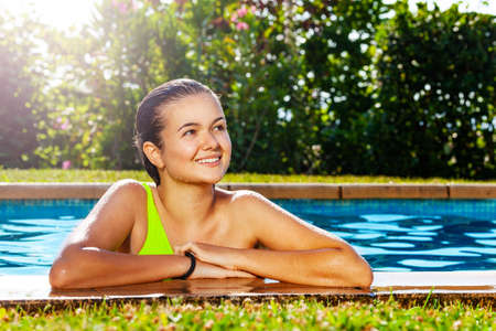 Girl on the border of outdoor swimming pool in the garden with big smile
