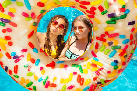 Two happy girls inside the inflatable buoy smile wearing near swimming pool in sunglasses with kiss gesture Reklamní fotografie