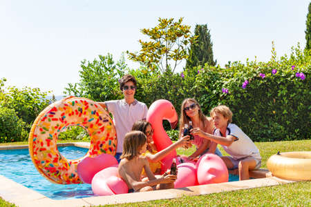 Group of happy young kids drink soda sitting in the pool with inflatables toys having fun