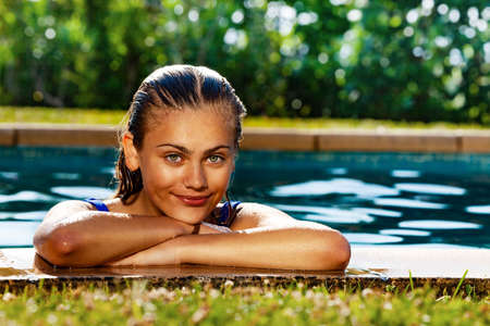 Beautiful young girl lay on hands on the border of outdoor swimming pool in the garden and smile in blue bikini Archivio Fotografico