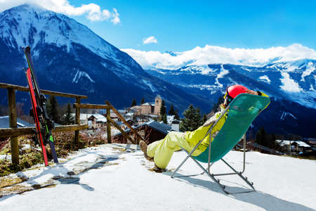 Young woman rest in the deck chair near pair of ski observing mountains and Alpine peaks Archivio Fotografico