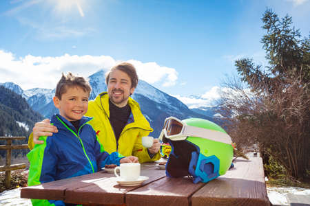 Father in ski outfit hug holding by shoulder little boy enjoy lunch break over mountain view after skiing