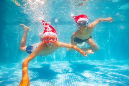 Two cool boys in scuba masks dive and swim underwater wearing Santa Claus hat in the pool