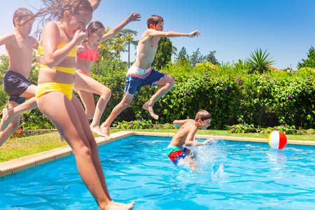 Boys and girls in a group jump in water pool outside during summer vacation
