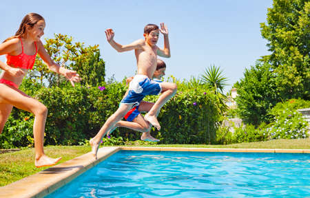 Happy boy in a group of friends jump into water of swimming pool together splashing down and lifting hands