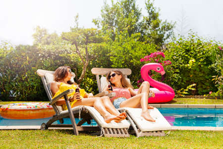 Two beautiful smiling teenage girls in shades celebrate with soda bottle sitting on the deck chair near pool