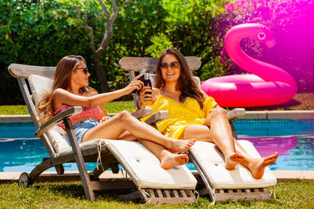 Two cute girls rest on pool chaise celebrate and drink long drinking soda laughing in sunglasses