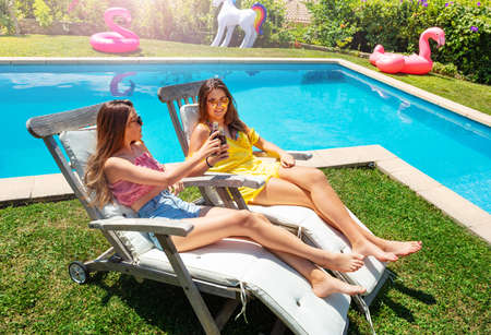 Two cute teenage girls rest on the chaise longue wearing sunglasses and drink cold cola Archivio Fotografico