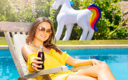 Happy beautiful teenage girl sit and rest on the chaise longue over blue pool drinking soda