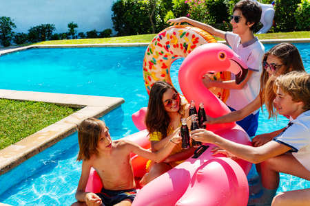 Group of teenage boys and girls play, chat, drink soda celebrating sitting on the border pool with inflatable buoys
