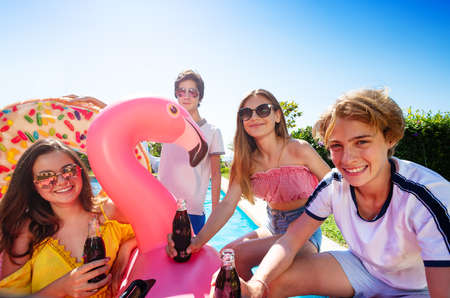 Teenage boys and girls chat, drink soda celebrating sitting on the border pool with inflatable buoys