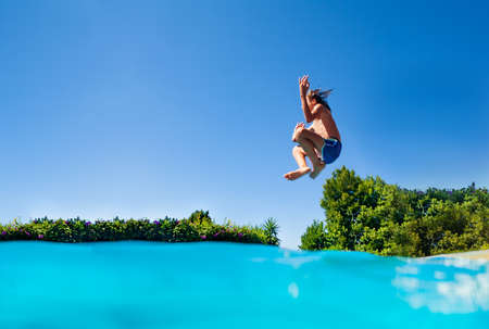 Profile photo of the boy jump high in action happy pose with lifted hands dive in the outdoor swimming pool
