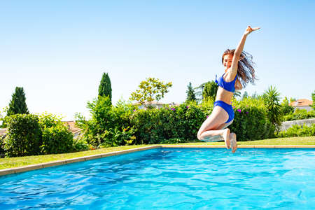 Beautiful girl jump in mid air into the swimming pool view from side scream and smile with hands up in funny pose