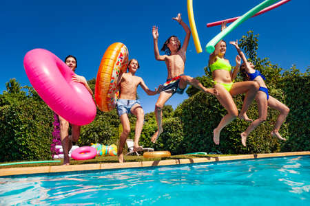 Group of teenage children have fun in the swimming pool diving with inflatable toys doughnuts jump and splash in the water