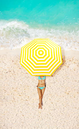 View from above of woman on a beach under umbrella taking sun bath