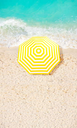 View from above of beach umbrella on the sand near ocean surf waves