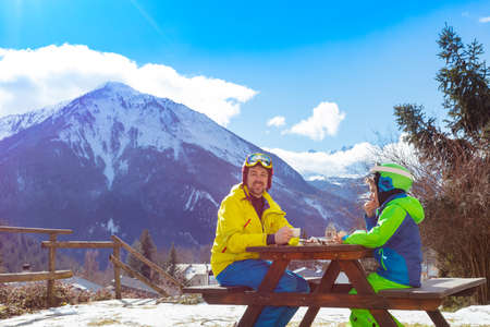 Father sit with young boy in ski outfit enjoy lunch break over mountain view after skiing Archivio Fotografico