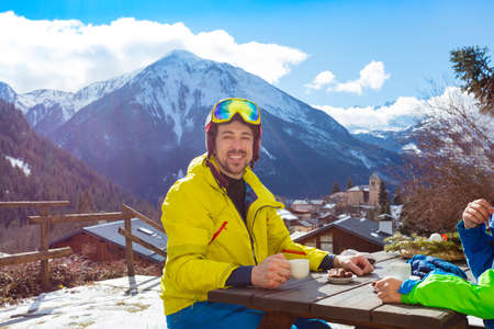 Happy smiling man in wear ski helmet drink tea in cafe over mountain view panorama during lunch Archivio Fotografico