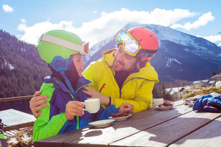 Father hug holding by shoulder little boy in ski outfit enjoy lunch break over mountain view after skiing Archivio Fotografico