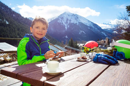 Happy boy lunch outside after ski in outdoor cafe with tea and cake on the table over mountain view Archivio Fotografico