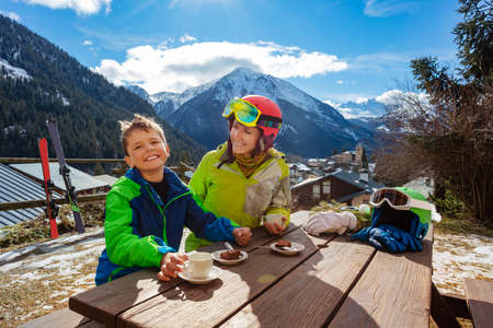 Laughing boy in cafe lunch with mom after ski smiling and talking over mountain panorama Archivio Fotografico