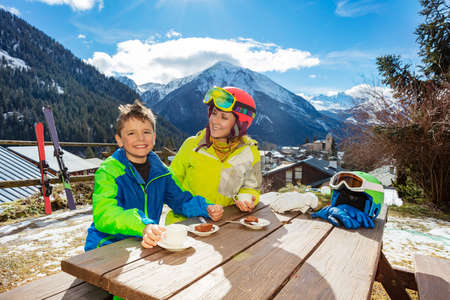 Mother look at and smile to a little boy in ski outfit sit, enjoy lunch break over mountain view after skiing Archivio Fotografico
