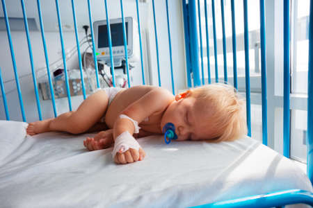 Cute small toddler sleep in hospital with catheter in his hand and pacifier Archivio Fotografico