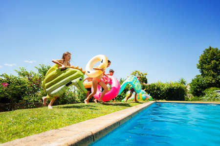 Group of many young kids run and jump into the swimming pool holding inflatable buoy toys diving in the water