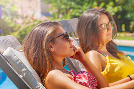 Two beautiful teen girls rest near pool chaise long drinking soda and laughing wearing sunglasses