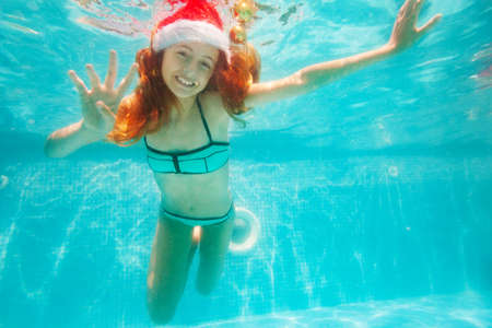 Happy girl dive and swim underwater wearing Santa Claus hat in the pool smile on her New Year vacation