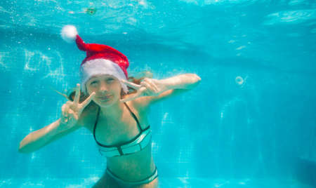Happy girl pose underwater wearing Santa Claus hat in the pool diving and swimming Archivio Fotografico