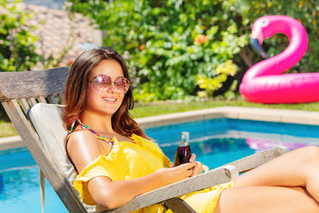Young teenage girl sit on the chaise longue near pool during summer vacation Archivio Fotografico