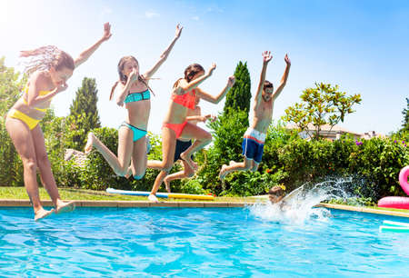 Happy kids in a group of friends jump into water of swimming pool together splashing down and lifting hands