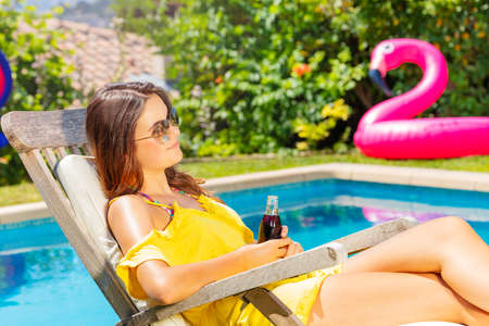 Profile portrait of a beautiful teenage girl sit and rest on the chaise longue over blue pool drinking soda