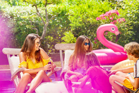 Two girls with friends relax and sit on the deck pool chairs drinking soda, chatting, smiling Archivio Fotografico