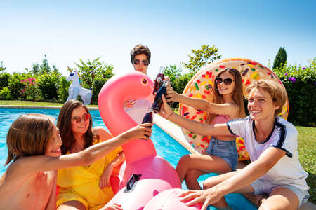 Group of teenage kids play chat and drink soda celebrating sitting on the border pool with inflatable buoys