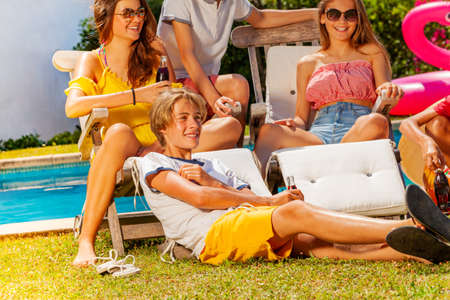 Boys with group of friends drinking soda chatting sit by the pool near deck chair, partying Archivio Fotografico
