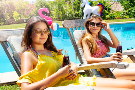 Close portrait of two cute girls on chair near pool holding cold soda wearing shades Archivio Fotografico