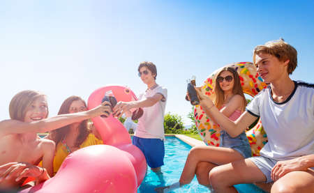 Many teenage kids play chat and drink soda celebrating sitting on the border pool with inflatable buoys