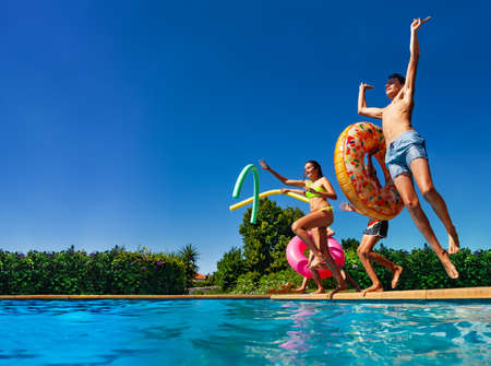 Many of happy teenage kids dive in the swimming pool water throw inflatable toys lifting hands have fun