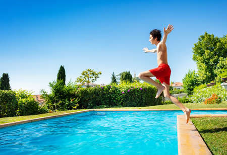Handsome boy jump in mid air into the swimming pool water view from side with hands up